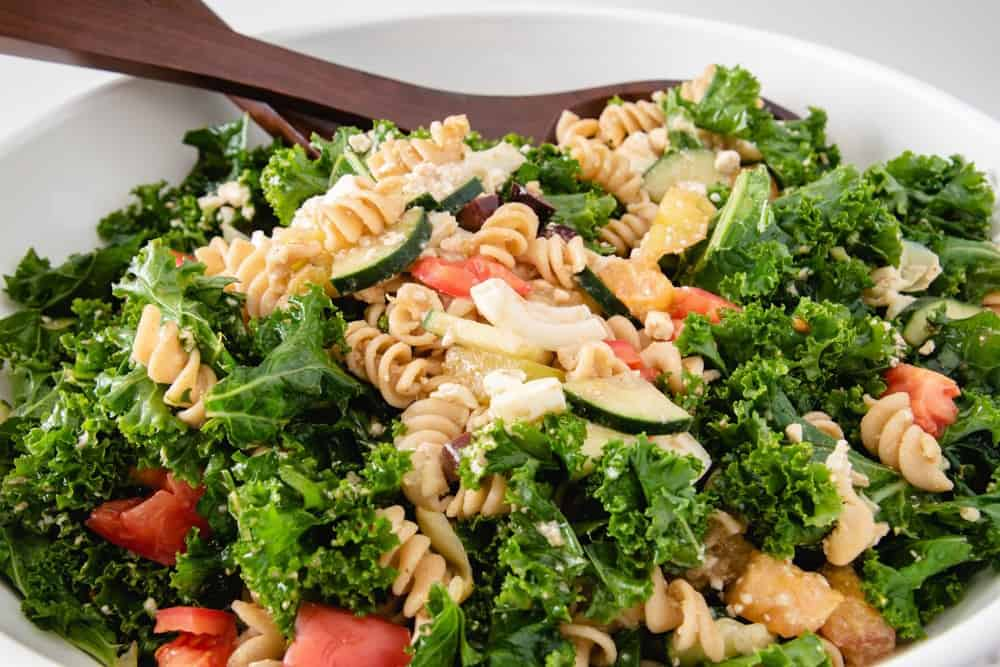 This easy kale salad recipe is a great clean out the fridge meal! It's full of healthy ingredients, with a super simple balsamic dressing to top it off. Enjoy this simple summer salad with your family today! #healthyrecipes #healthykalesalad