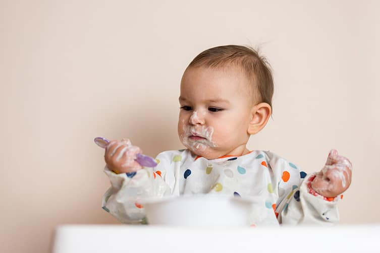 Messy baby looking at spoon with yogurt on it