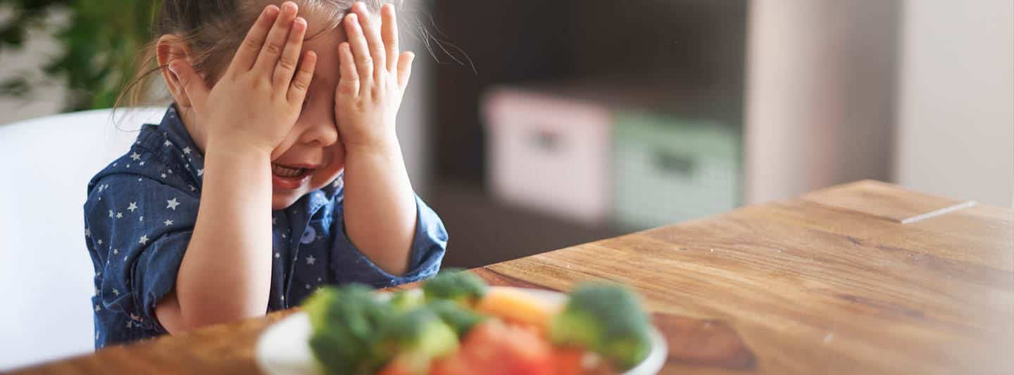 Child hiding behind hands with plate of veggies on table