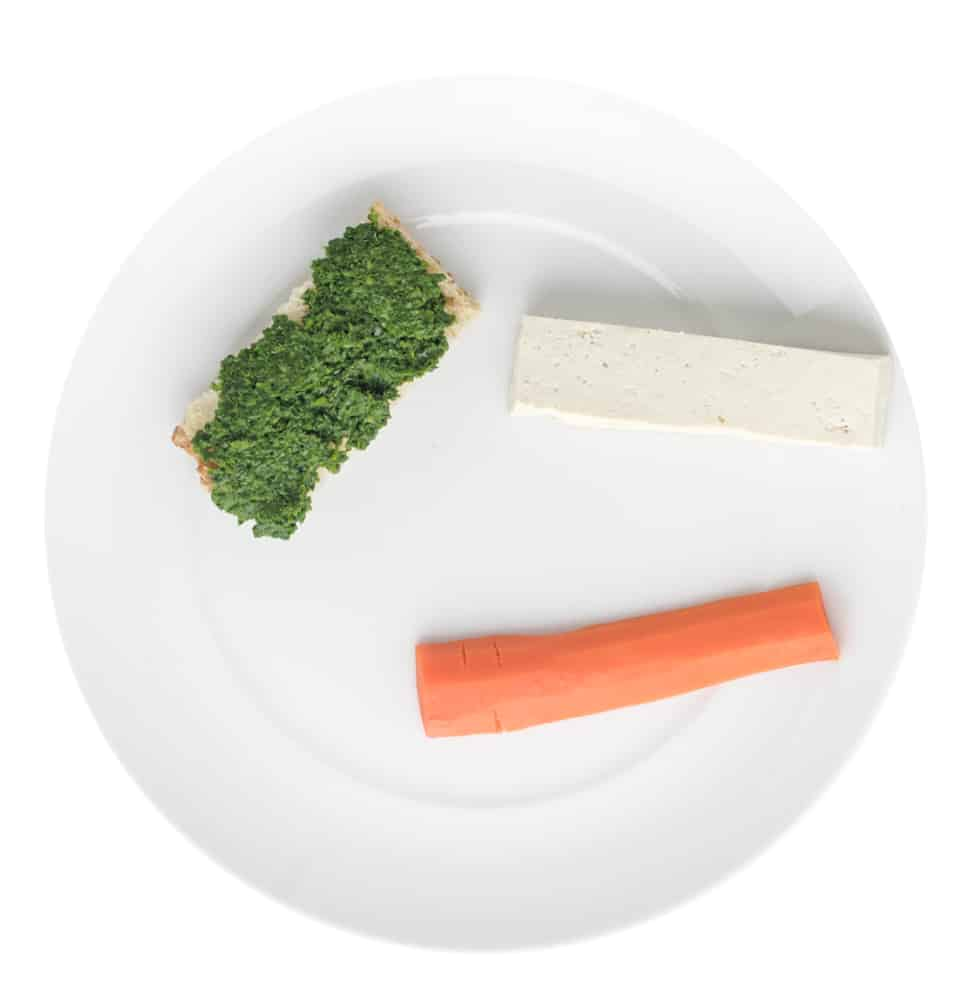 Plate with kale pesto on finger of bread, finger of tofu and a finger of carrot