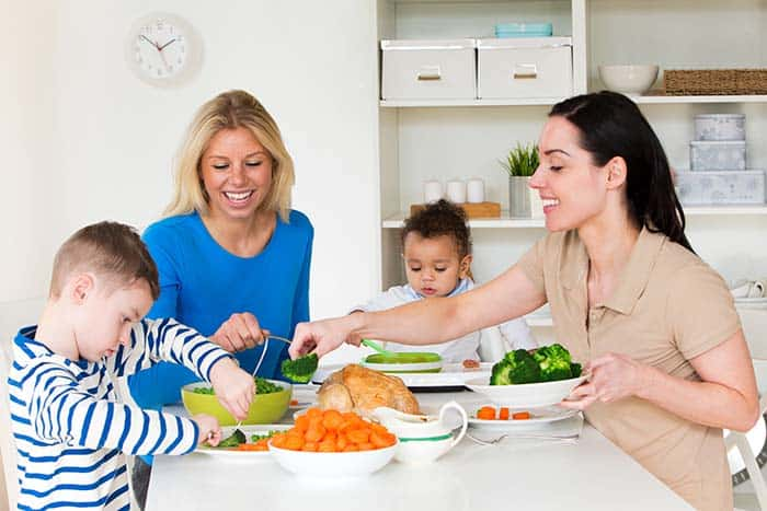 Two moms and two kids enjoying eating together at family meal